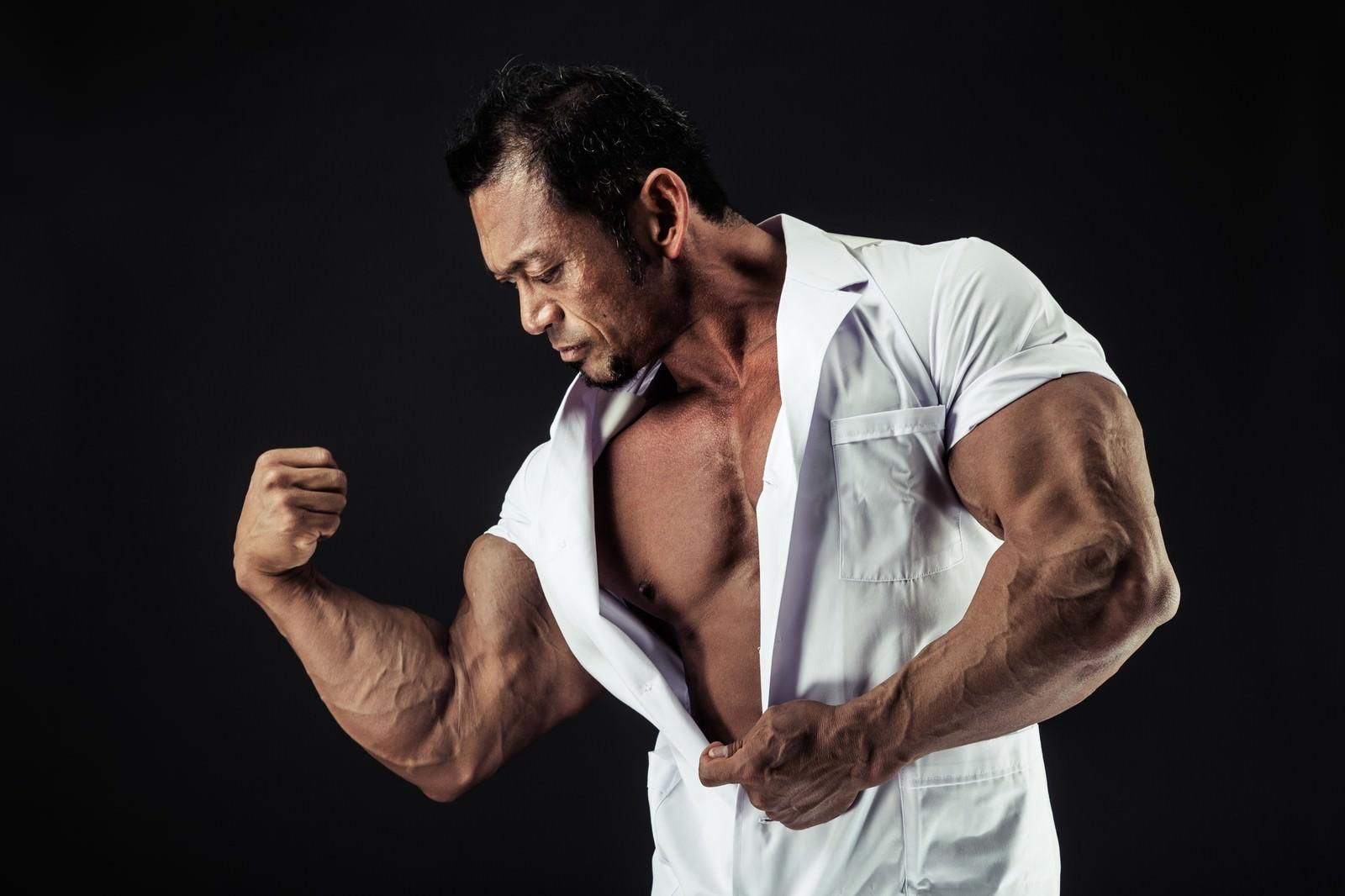 「極太の上腕二頭筋をアピールする歯科医」の写真[モデル:パルンボ井若]