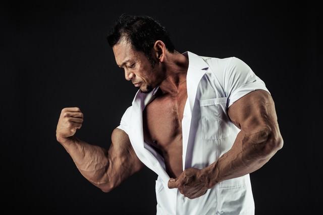 極太の上腕二頭筋をアピールする歯科医の写真