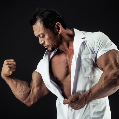 「極太の上腕二頭筋をアピールする歯科医」の写真素材
