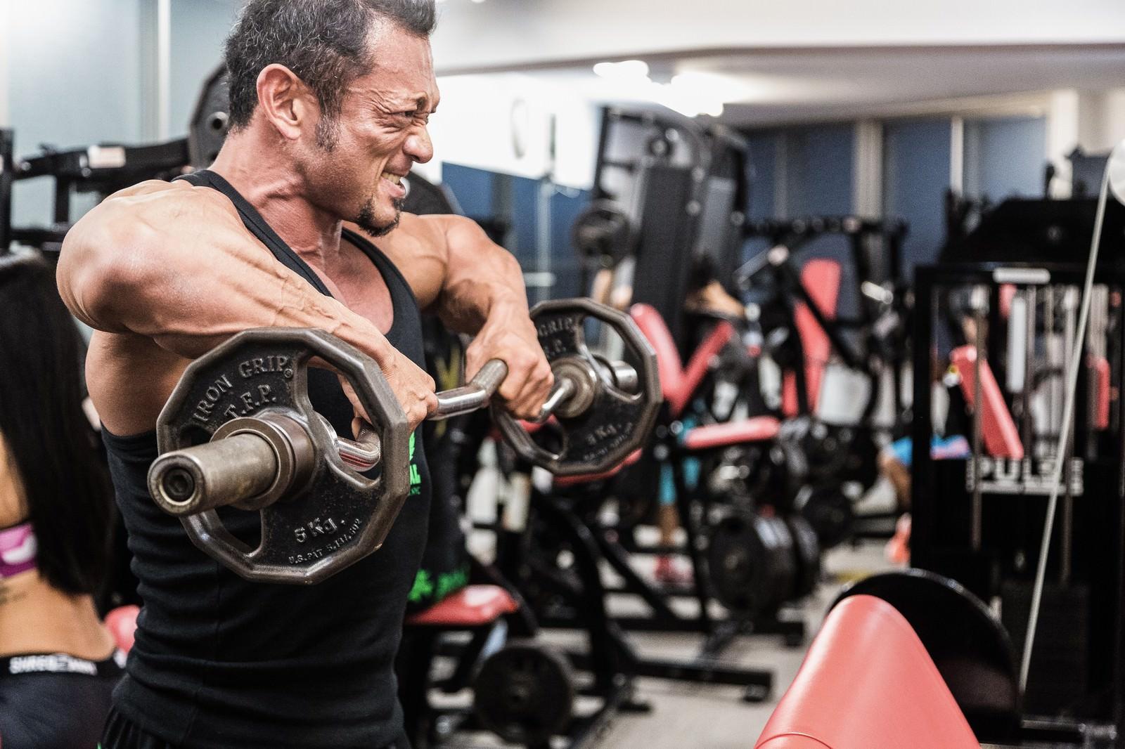 「バーベルで筋肉に負荷をかけるボディビルダー」の写真[モデル:パルンボ井若]