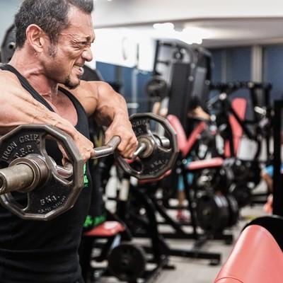 「バーベルで筋肉に負荷をかけるボディビルダー」の写真素材