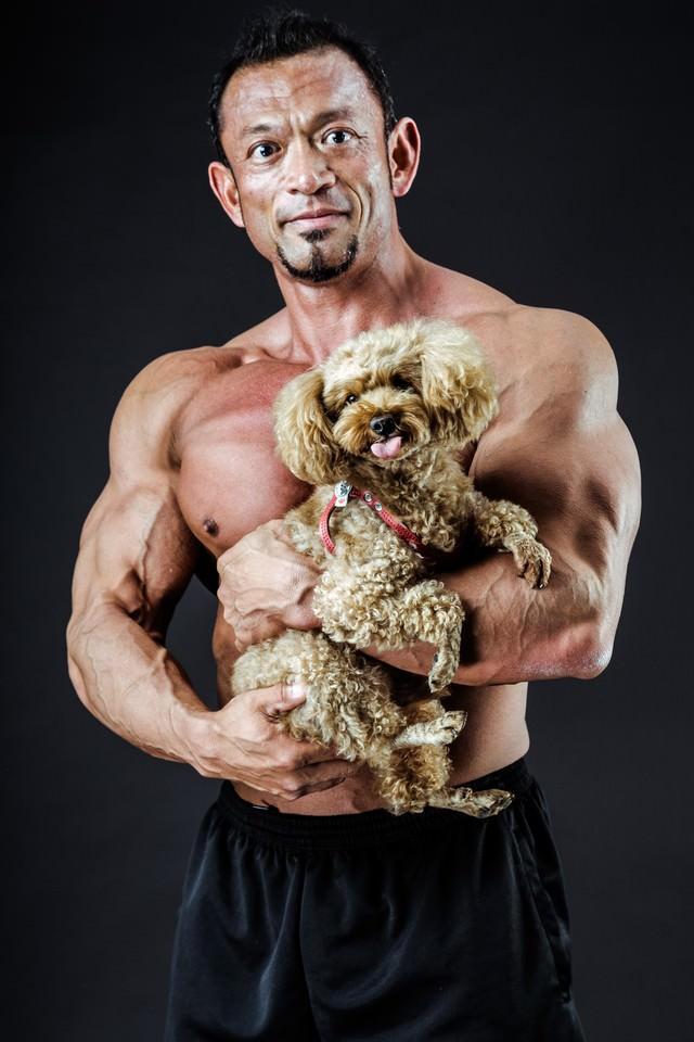 子犬を抱くボディビルダーの写真