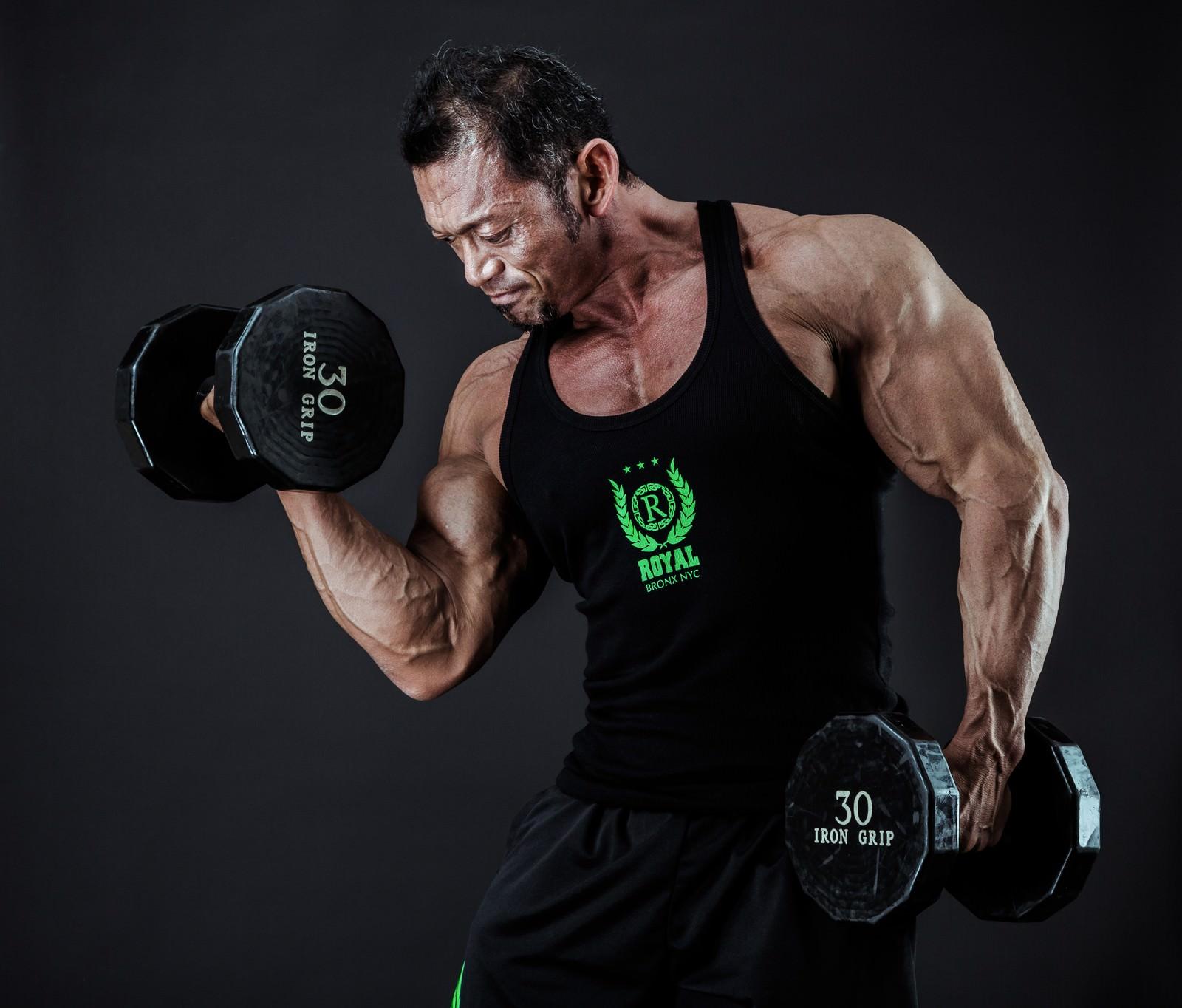 「ダンベルで上腕二頭筋を鍛えるボディビルダー」の写真[モデル:パルンボ井若]