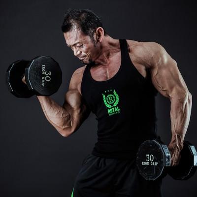 「ダンベルで上腕二頭筋を鍛えるボディビルダー」の写真素材