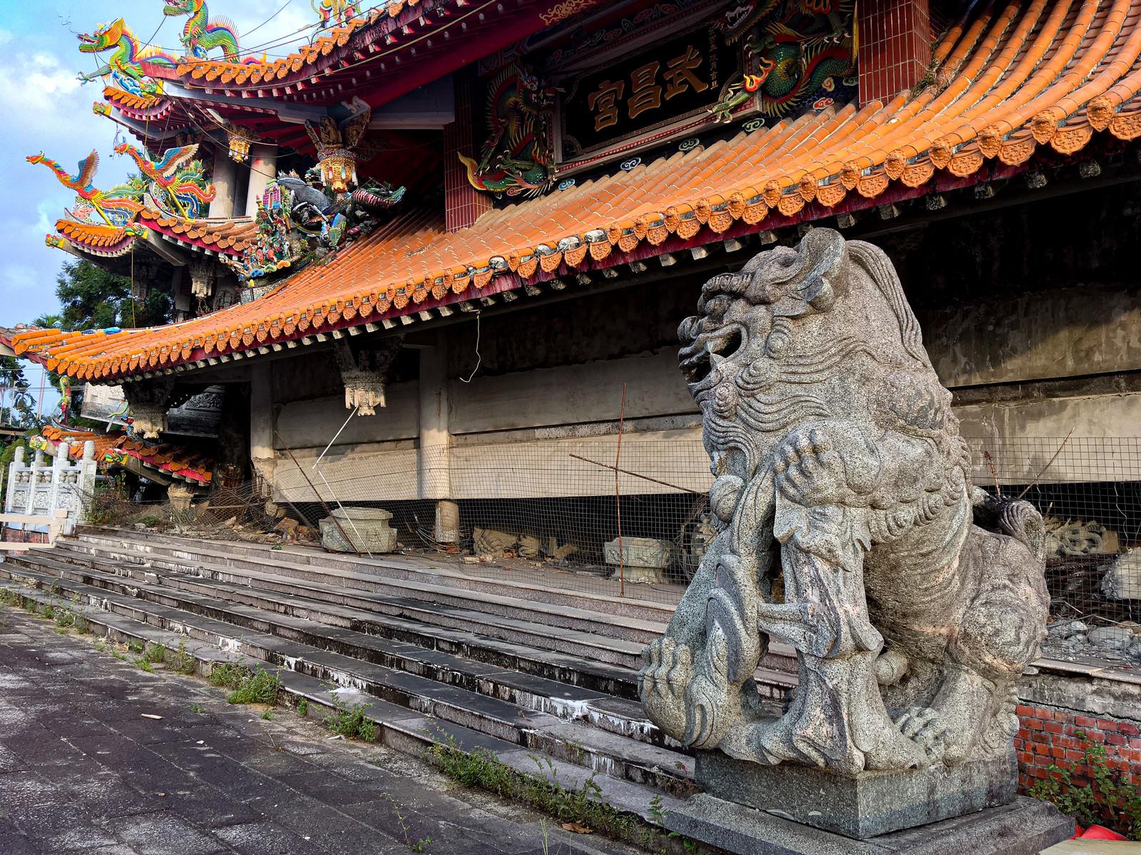 「地震で崩れた寺院に鎮座する狛犬の石像(台湾)」の写真