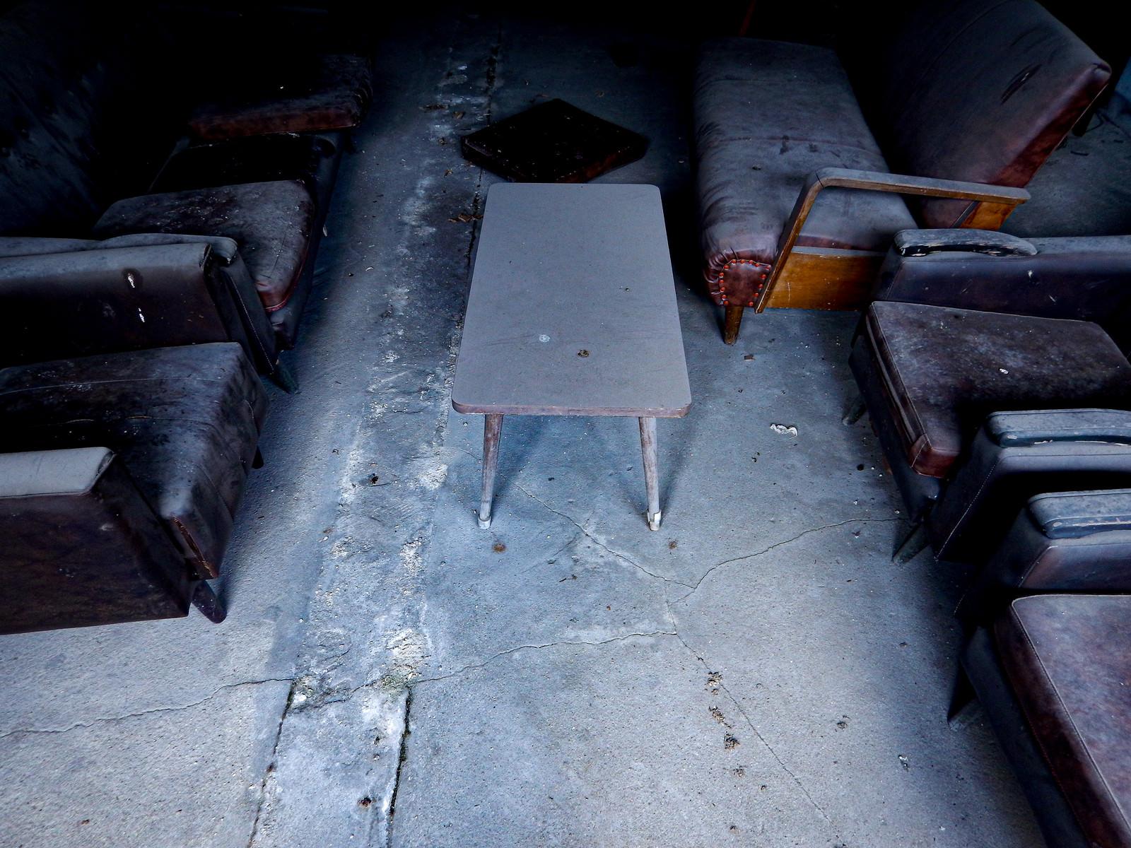 「廃屋の埃まみれのテーブルとソファー(応接室跡)」の写真