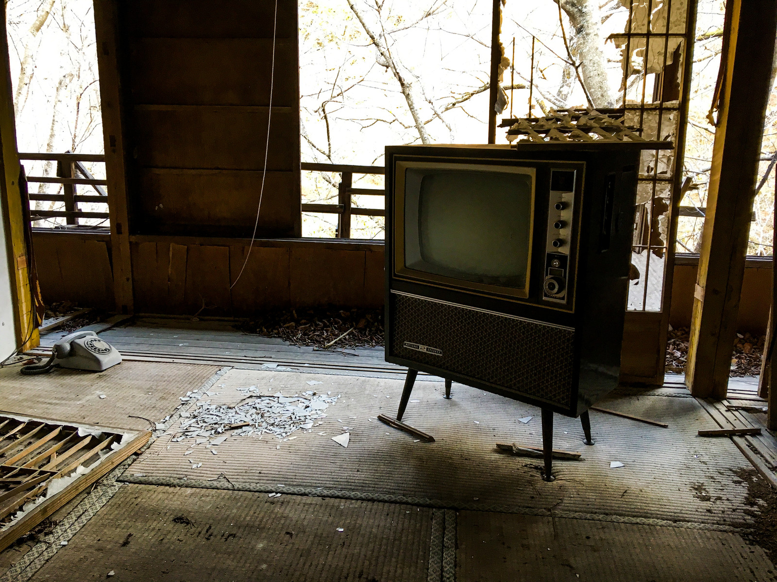 「廃屋に残された古いアナログテレビ」の写真