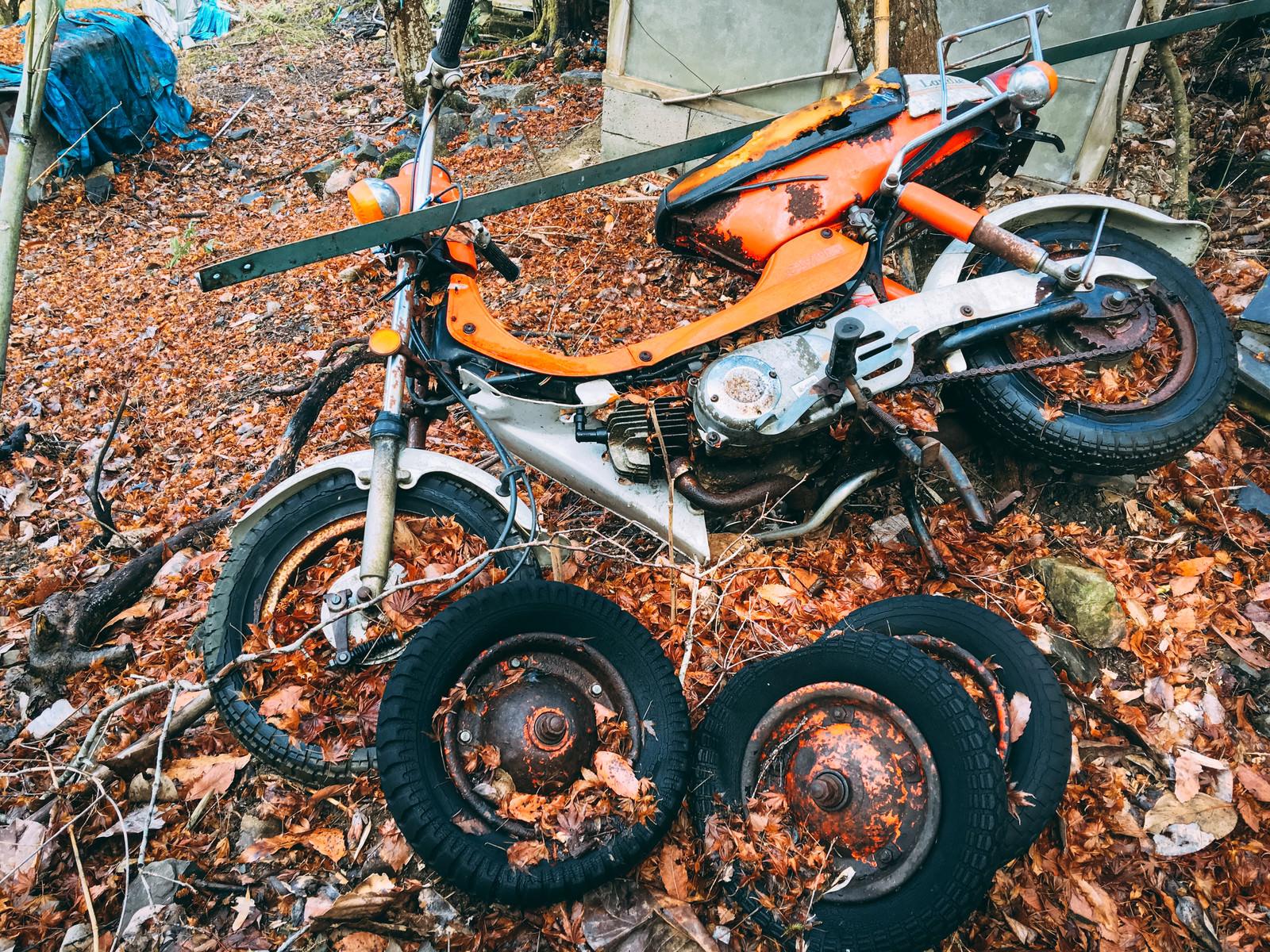 「不法投棄されたバイクと複数のタイヤ」の写真