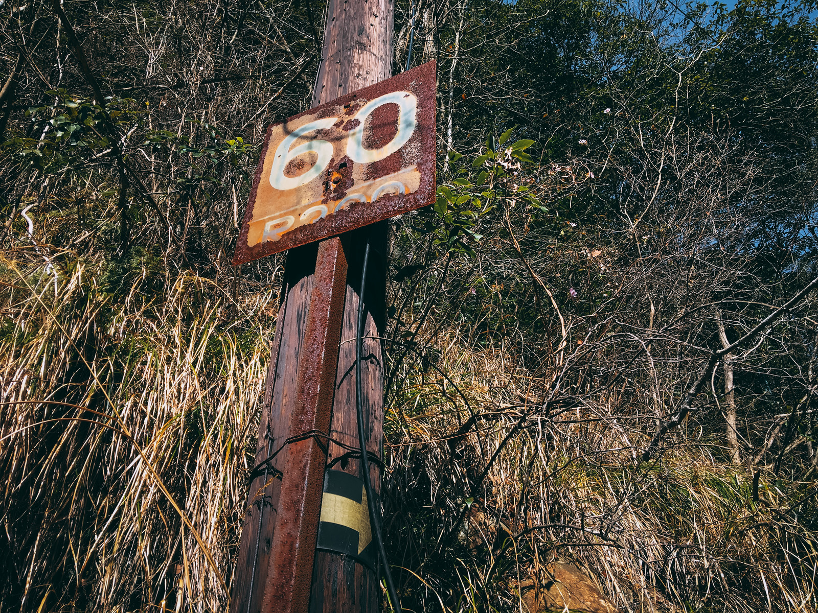 「60と書かれた錆びついた鉄看板(JR福知山線廃線敷)」の写真