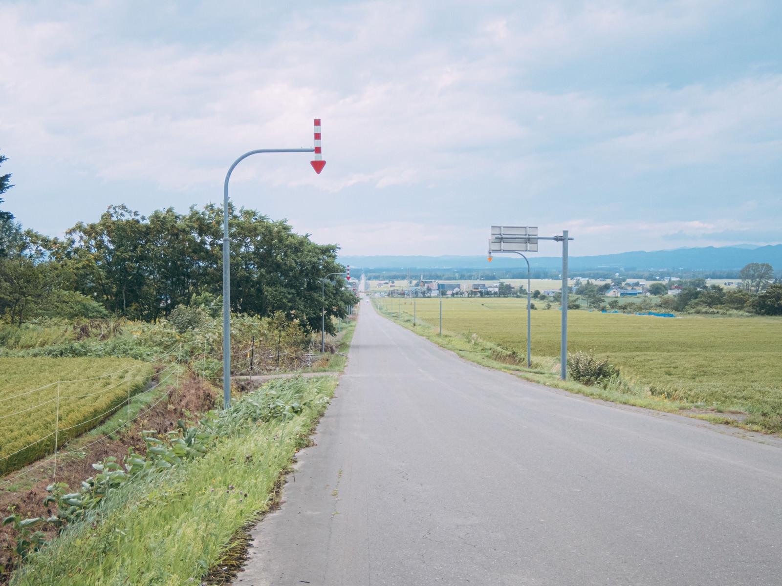 「北海道の長い一直線の道路と矢羽根付きポール」の写真