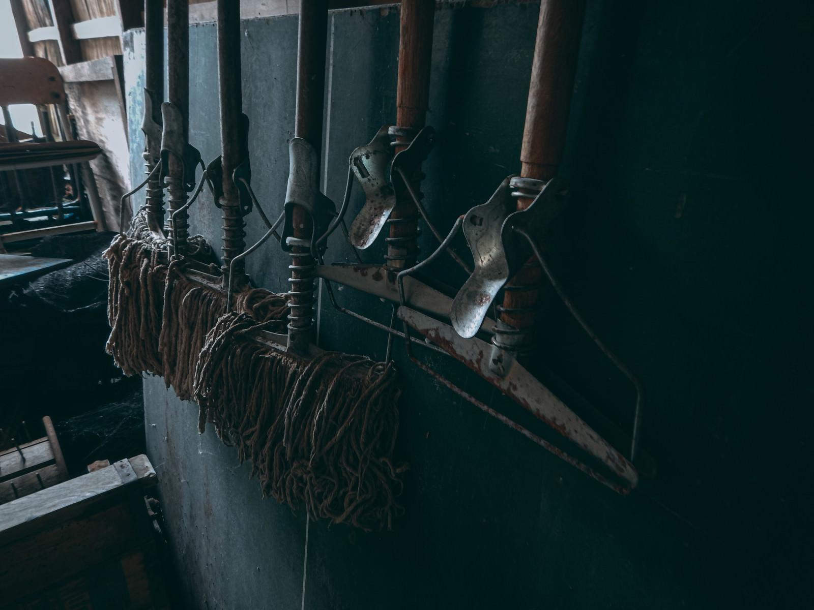 「壁に吊るされたモップ(廃墟)」の写真