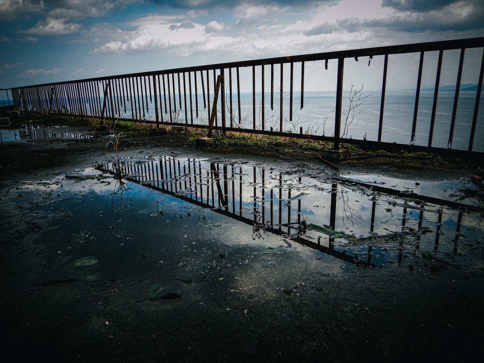 「水たまりに写り込んだ空と壊れた柵」の写真