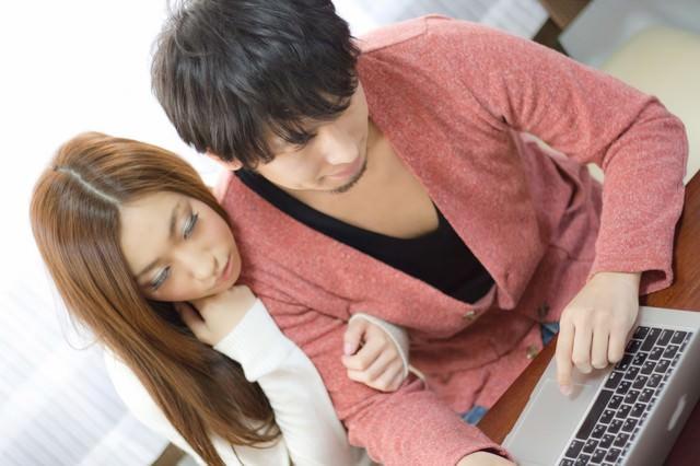 ノートパソコンでネットを楽しむ二人(恋人)の写真