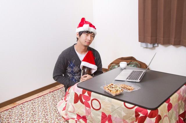 クリスマスに寂しく一升瓶を抱える男性の写真