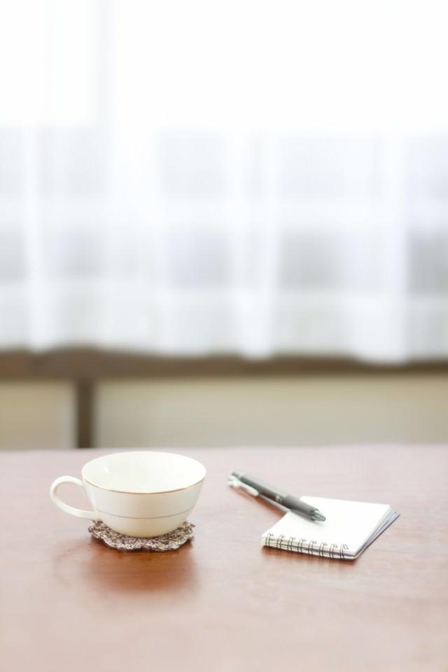 コーヒーカップとメモ帳の写真