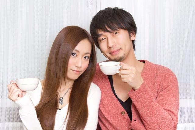 二人でコーヒーカップを持つ若い夫婦の写真