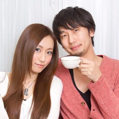 「二人でコーヒーカップを持つ若い夫婦」の写真素材