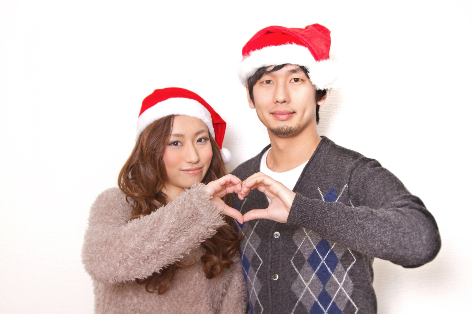 「クリスマスに指でハートの形を作る恋人」の写真[モデル:大川竜弥 北野佑々]