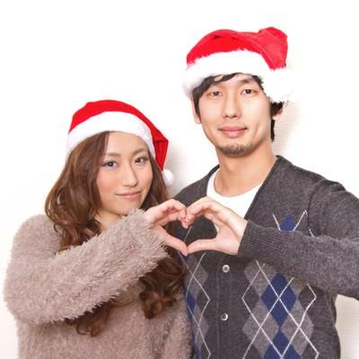 「クリスマスに指でハートの形を作る恋人」の写真素材