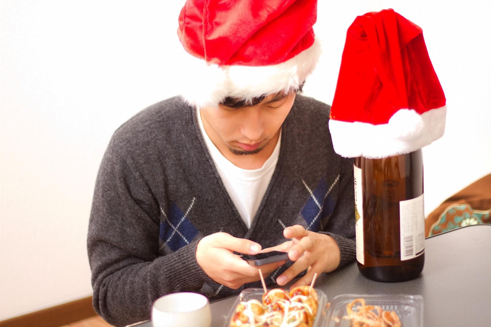 「メールが来ているかスマホを確認するサンタ帽をかぶったクリぼっち」の写真[モデル:大川竜弥]