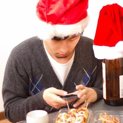 「メールが来ているかスマホを確認するサンタ帽をかぶったクリぼっち」の写真素材
