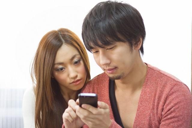 スマホでショップ情報を確認する恋人の写真