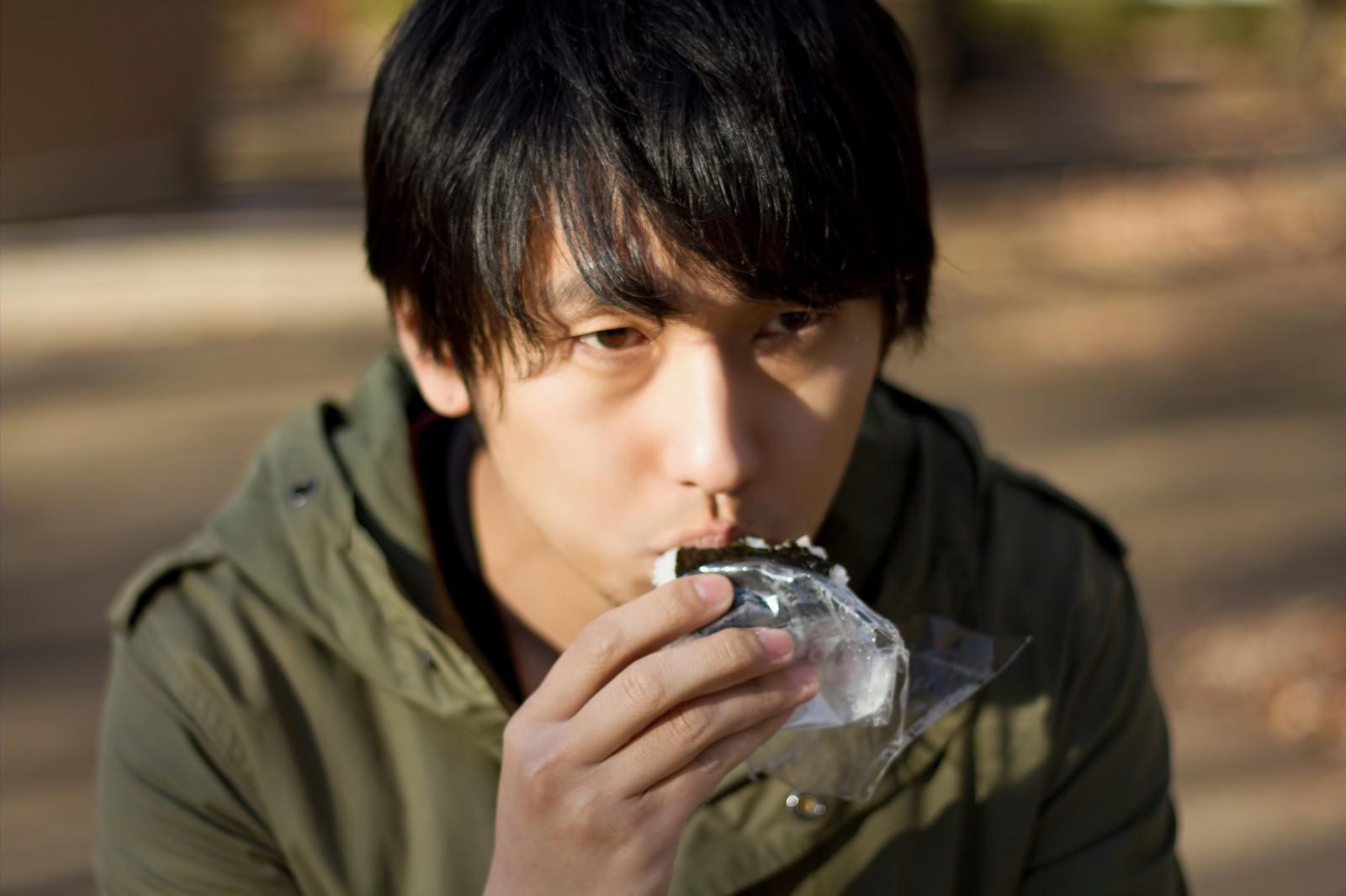 「外でコンビニおにぎりを食べる孤独な男性」の写真[モデル:大川竜弥]