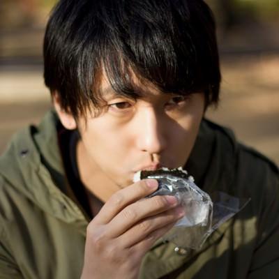 外でコンビニおにぎりを食べる孤独な男性の写真