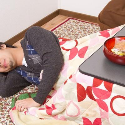 「こたつでうっかり寝てしまう男性」の写真素材