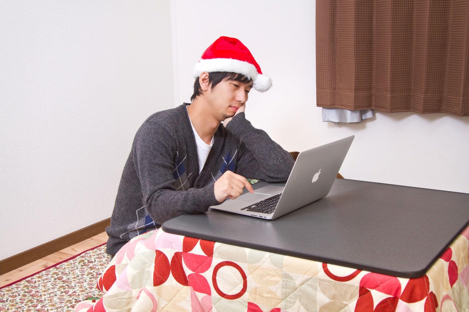 『世間はリア充ばかりか』とクリスマスをネットしながら孤独に過ごす男性のフリー素材