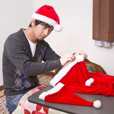 「クリスマスの女性用衣装を準備して雰囲気だけ楽しむ男性」の写真素材
