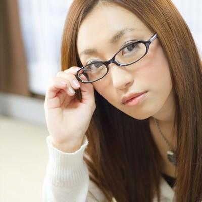 「メガネの位置を直す女性」の写真素材