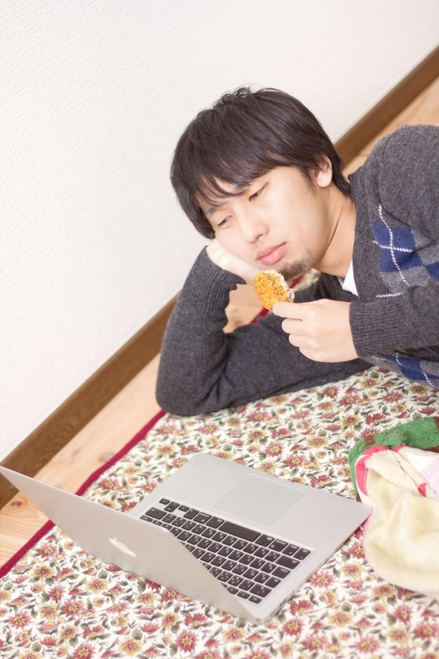 横になり寝ながらノートパソコンを触る男性の写真