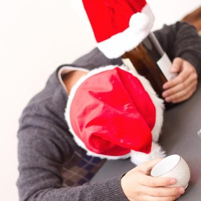 クリスマスにこたつの上で酔いつぶれる男性の写真