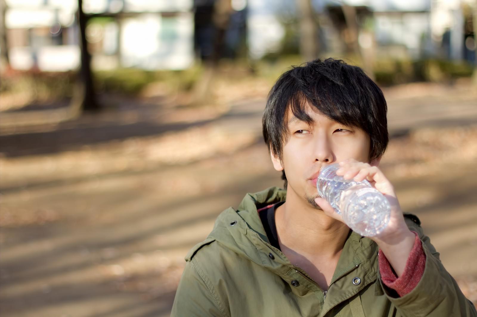寂しく公園でペッドボトルの水を飲む男性