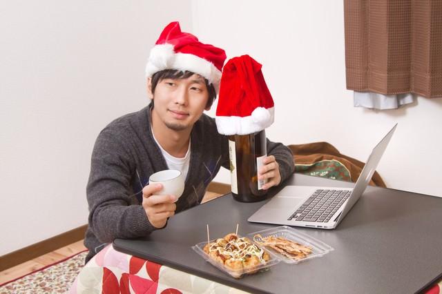 クリスマスにひとりで晩酌する男性の写真