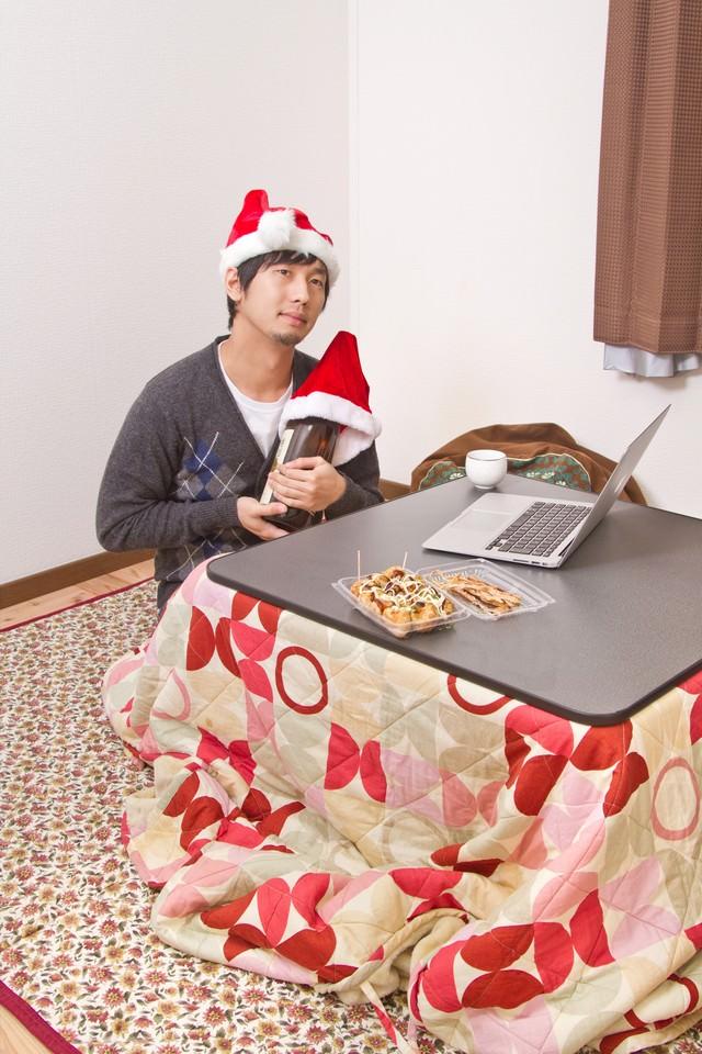 サンタ帽をかぶり酒瓶と聖なる夜を過ごす切ない表情のクリぼっちの写真