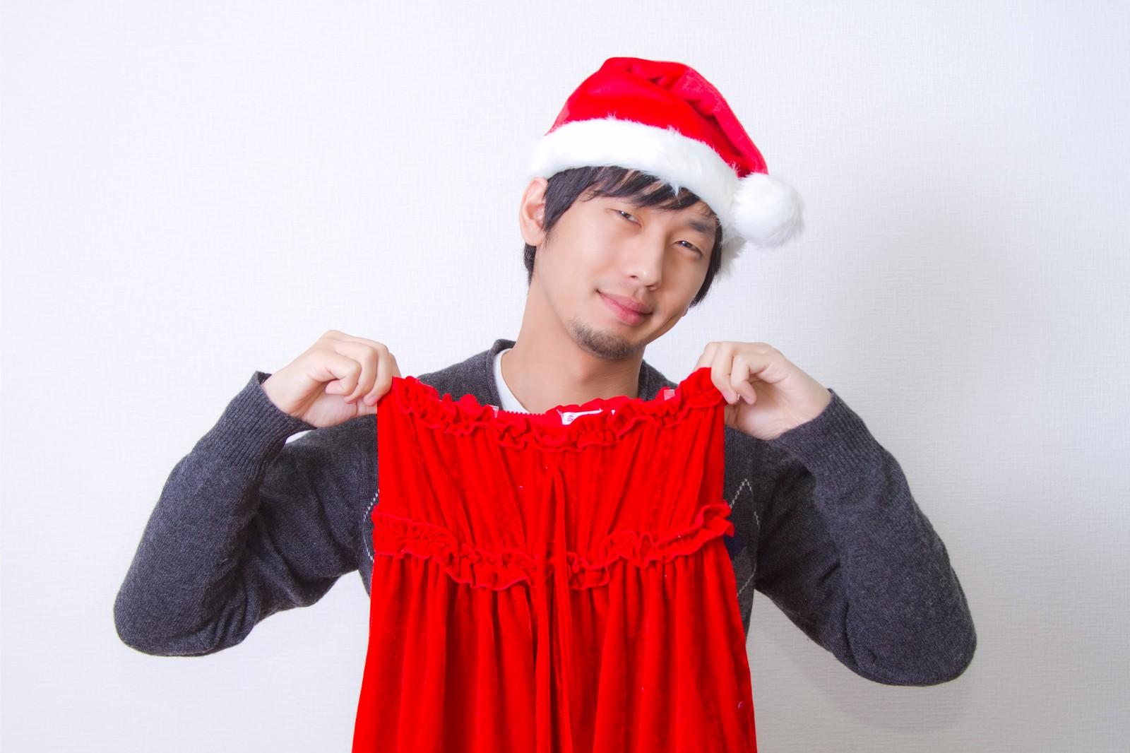 「サンタの女性用コスプレのスカートを持って苦笑いする男性」の写真[モデル:大川竜弥]