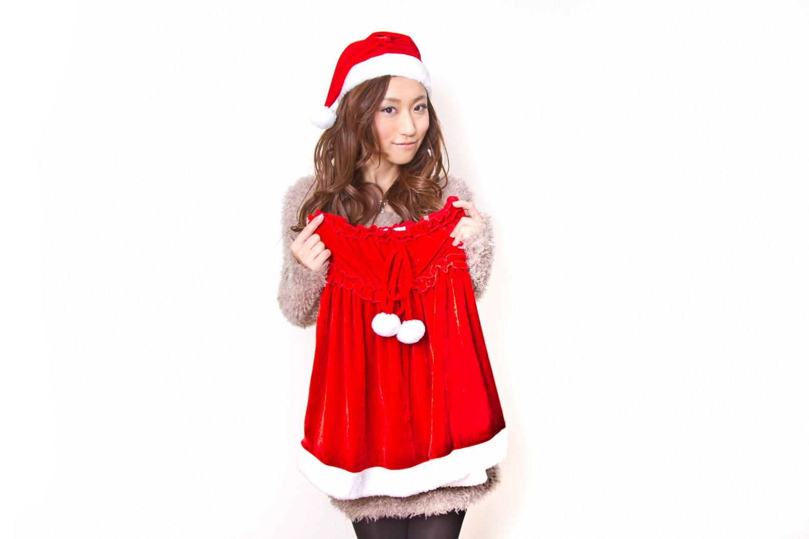 「女性用サンタの衣装を手に取る女性」の写真[モデル:北野佑々]