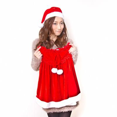 「女性用サンタの衣装を手に取る女性」の写真素材