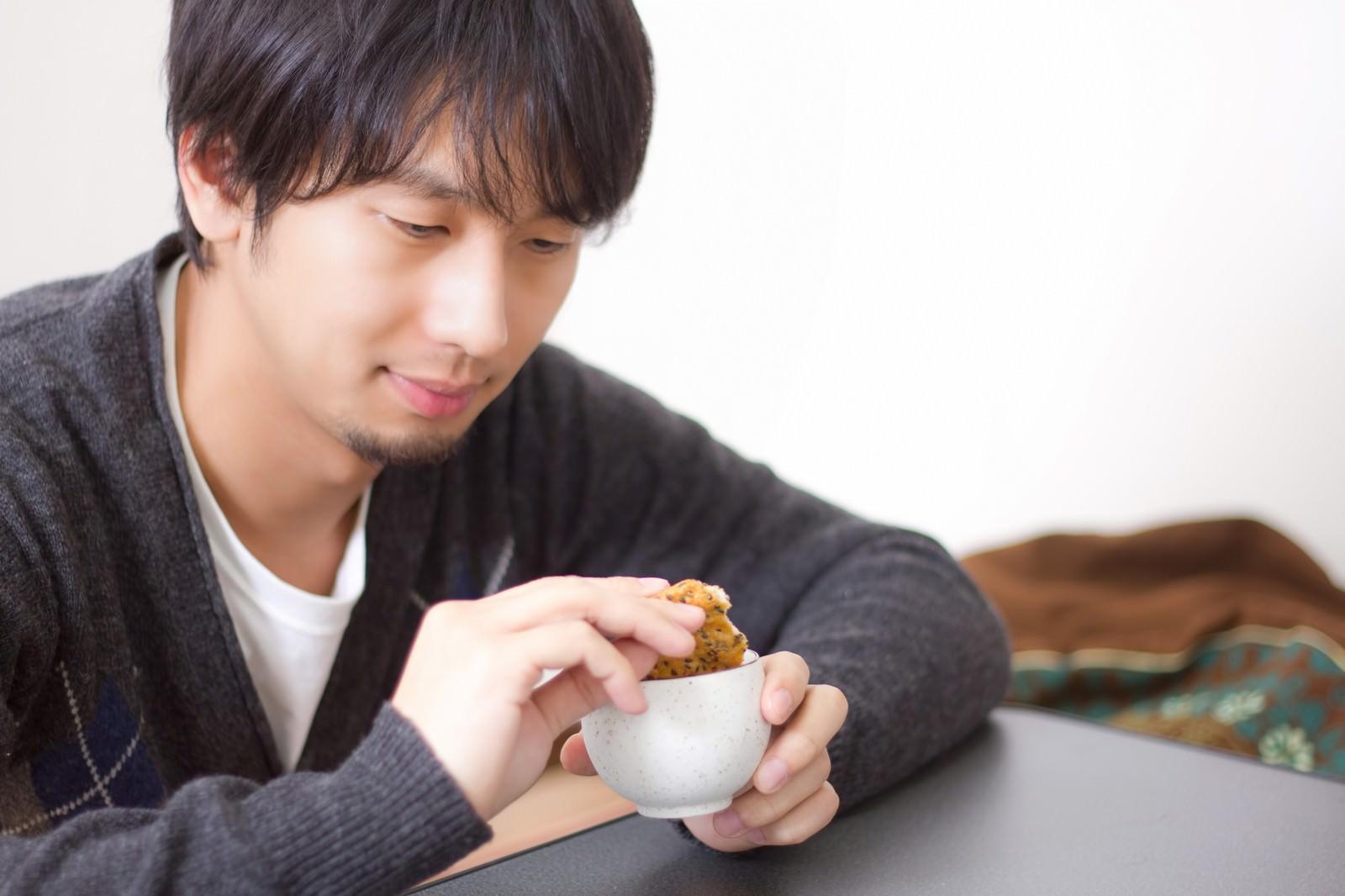 「せんべいをお茶につけてふやかす男性」の写真[モデル:大川竜弥]