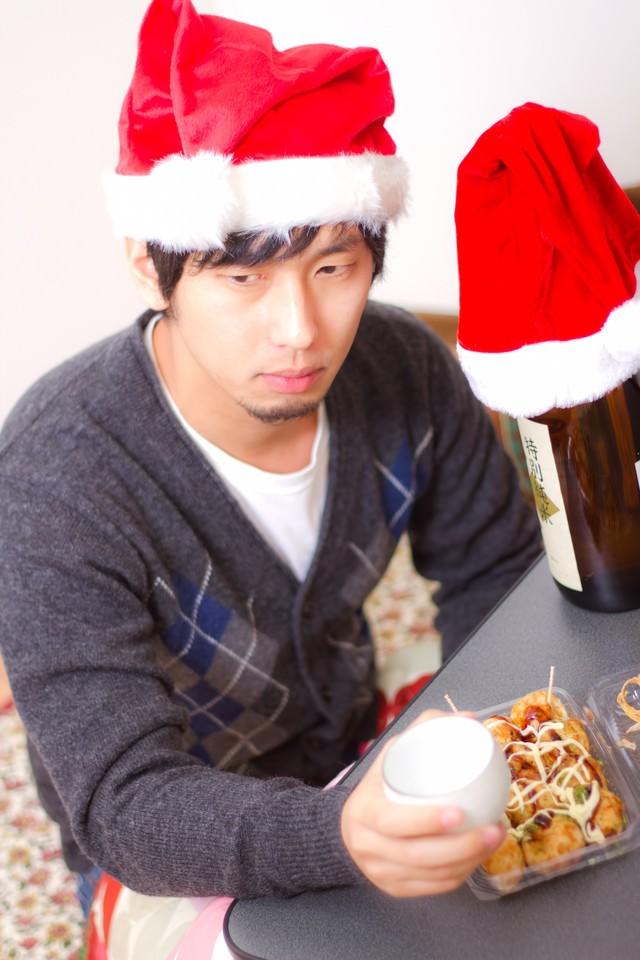 孤独なクリスマスでもお酒とおつまみがあれば負けない!表情の男性の写真