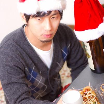 「孤独なクリスマスでもお酒とおつまみがあれば負けない!表情の男性」の写真素材