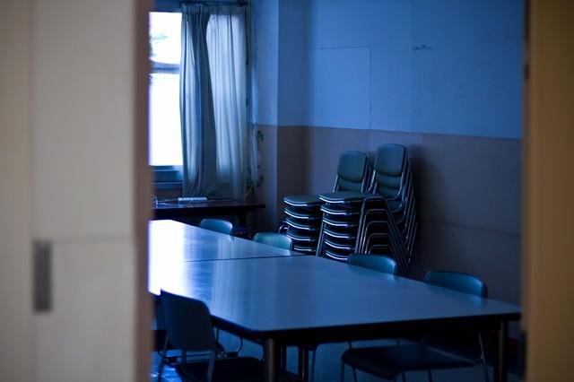 椅子を重ねた薄暗い会議室の写真