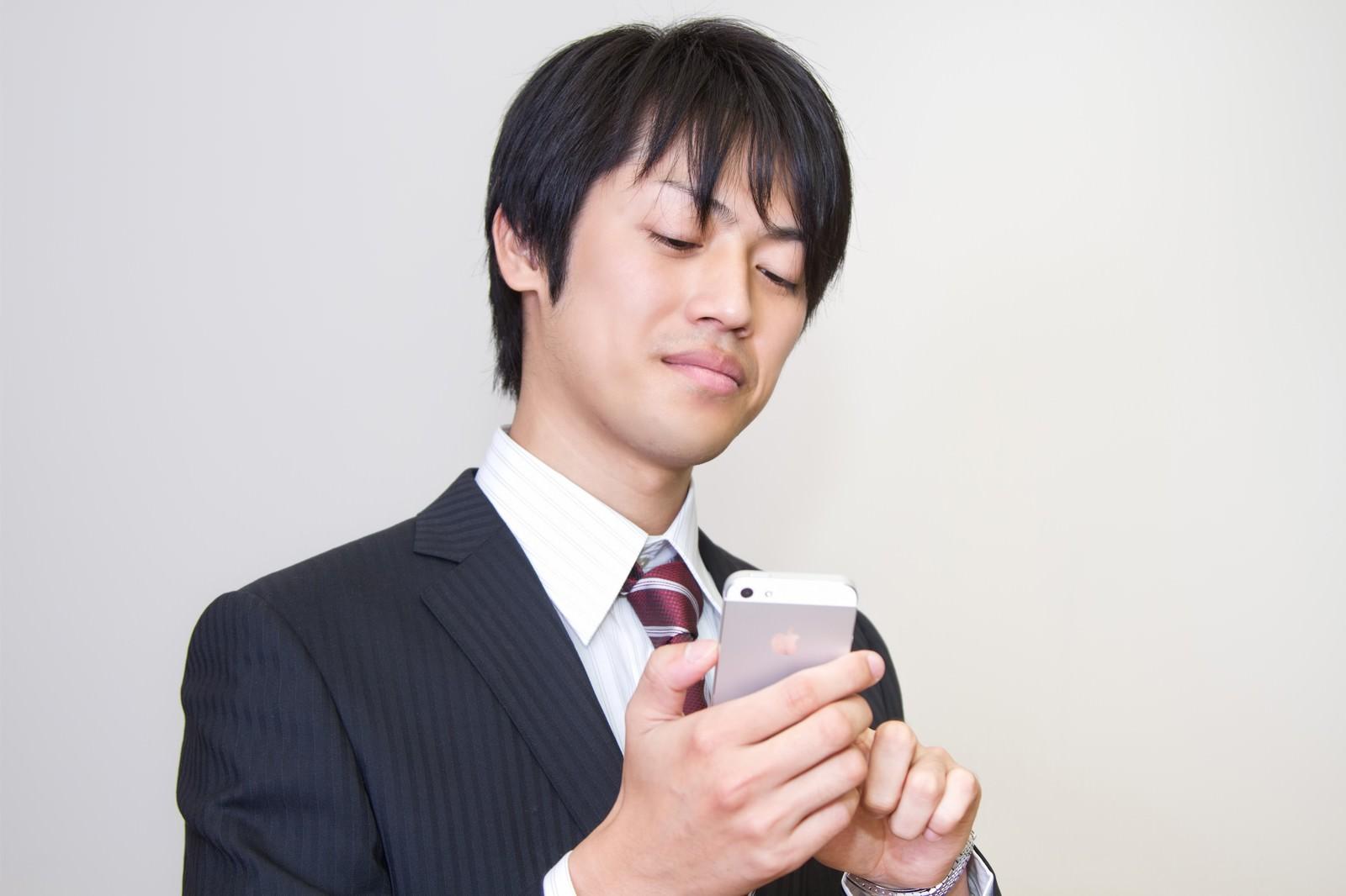 「ニヤニヤしながらスマホをいじるサラリーマン」の写真[モデル:Tsuyoshi.]