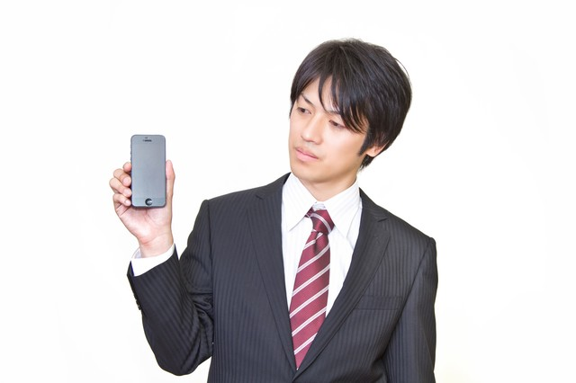 世代前のスマートフォンを手に持つサラリーマンの写真