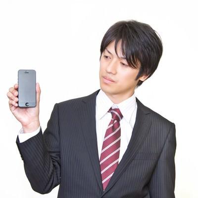 「世代前のスマートフォンを手に持つサラリーマン」の写真素材