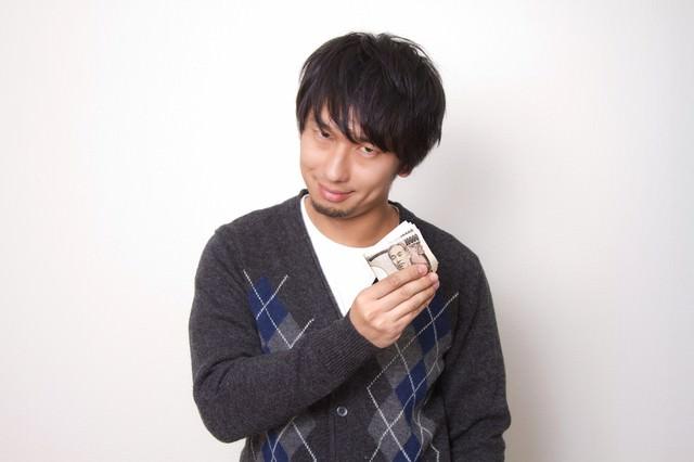 『計画通り!(ニヤリ』と萬札を見せる男性の写真
