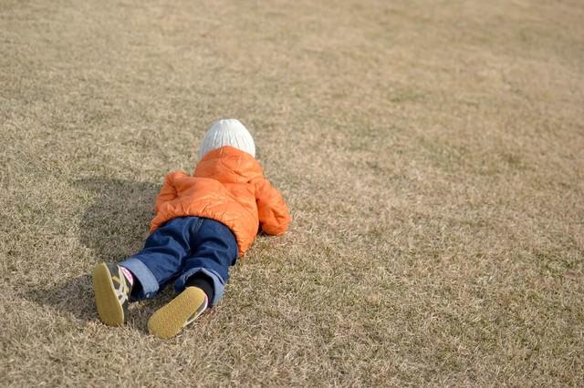 芝に寝転ぶ子供の写真