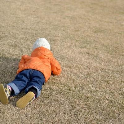 「芝に寝転ぶ子供」の写真素材